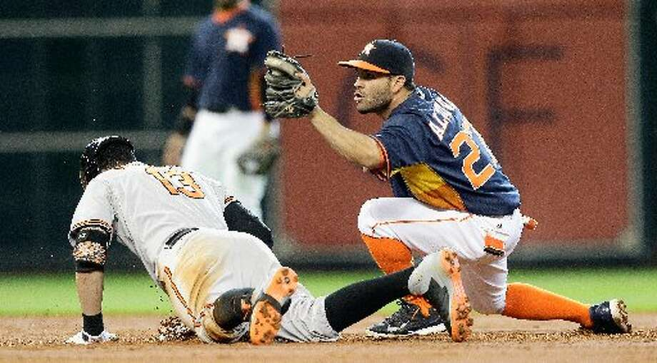 Manny Machado doubles in the third inning as Jose Altuve applies the tag. Photo: Bob Levey, Getty Images