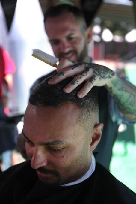 Abe Daniels of Santa Rosa has his hair cut by barber Chris Jennings of Walnut Creek's Str8 Edge Barbershop at the Sailor Jerry booth during the 2014 Bottlerock Napa Valley music, food and wine festival on Sunday, June 1, 2014 in Napa, Calif. Photo: Kevin N. Hume, The Chronicle