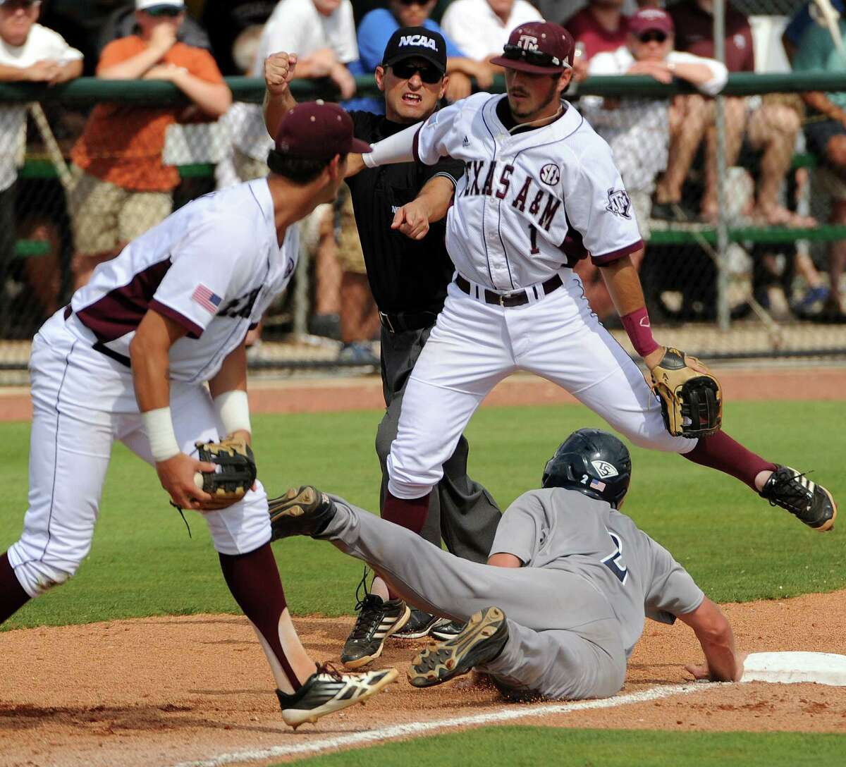 Rice's Shane Hoelscher, bottom, dives back to third base after being tagged out by Texas A&M's Logan Mottebrok, right, as Blake Allemand, right, jumps out of the way during the sixth inning of an NCAA baseball regional game, Sunday, June 1, 2014, at Reckling Park in Houston.