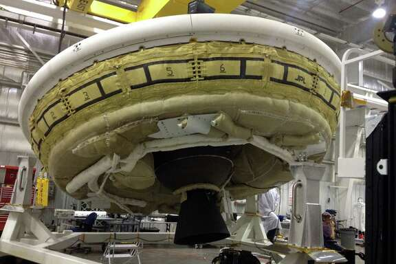 A saucer-shaped test vehicle holds equipment for landing large payloads on Mars in the Missile Assembly Building at the U.S. Navy's Pacific Missile Range Facility. The vehicle will test an inflatable decelerator and a parachute at high altitudes.
