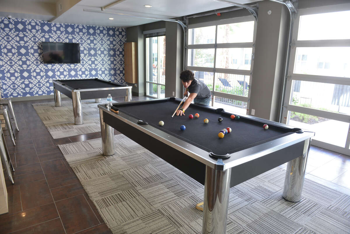 Tony Diaz plays at one of two pool tables in the Tobin Lofts building.