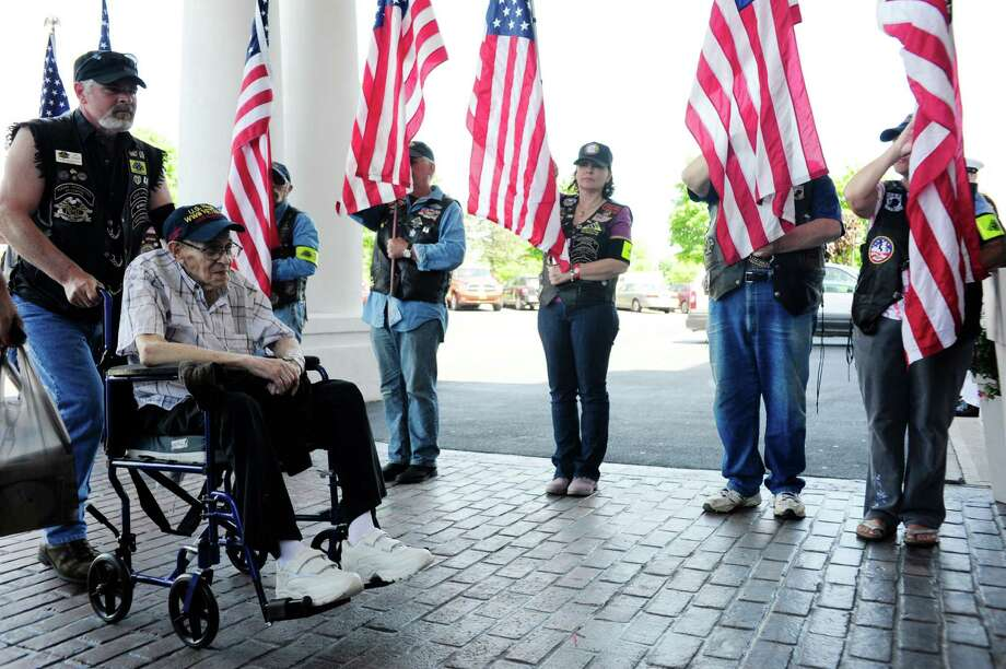 World War II Navy veteran, Don Latimer of Schenectady, is wheeled by Patriot Guard Rider Jim Diegel as other Patriot Guard Riders stand with flags during a remembrance ceremony to mark the 70th Anniversary of D-Day on Sunday, June 1, 2014, at the Holiday Inn Express in Latham, N.Y.  (Paul Buckowski / Times Union) Photo: Paul Buckowski / 00027085A