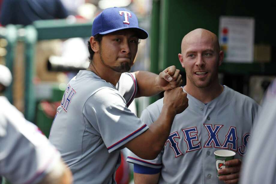 Rangers pitcher Yu Darvish (left), who fanned 12 in his fifth win, mimics batting with Chris Gimenez. Photo: Alex Brandon / Associated Press / AP