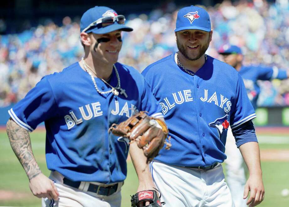 Toronto Blue Jays starting pitcher Mark Buehrle laughs with Blue Jays Brett Lawrie, left, while walking back to the dugout against Kansas City Royals during eighth inning  baseball action in Toronto on Sunday, June 1, 2014. (AP Photo/The Canadian Press, Nathan Denette) ORG XMIT: NSD116 Photo: Nathan Denette / CP