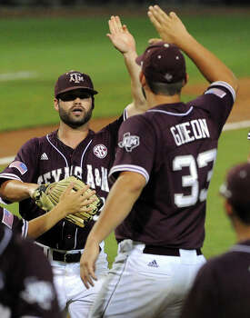 Texas A&M left fielder Jace Statum, left,  celebrates his foul out catch of Texas' Mark Payton with Ronnie Gideon during the fifth inning of an NCAA baseball regional game, Sunday, June 1, 2014, at Reckling Park in Houston. Photo: Eric Christian Smith, For The Chronicle