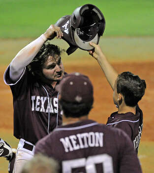 Texas A&M's Ryne Birk, left, celebrates his go-ahead run with ball boy Max Childress, son of head coach Rob Childress, during the fifth inning of an NCAA baseball regional game against Texas, Sunday, June 1, 2014, at Reckling Park in Houston. Photo: Eric Christian Smith, For The Chronicle