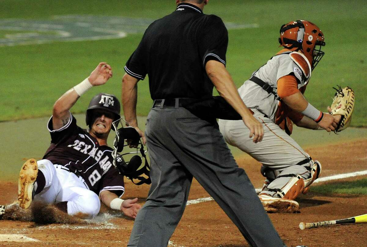 Texas A&M's Logan Nottebrook (8) slides safely past Texas catcher Tres Barrera to tie the game 1-1, during the second inning of an NCAA baseball regional game, Sunday, June 1, 2014, at Reckling Park in Houston.