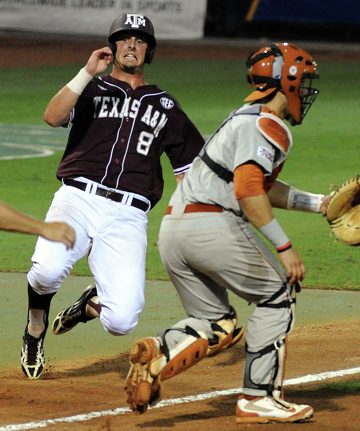 Texas A&M's Logan Nottebrook (8) slides safely past Texas catcher Tres Barrera to tie the game 1-1, during the second inning of an NCAA baseball regional game, Sunday, June 1, 2014, at Reckling Park in Houston. (AP Photo/Houston Chronicle, Eric Christian Smith)
