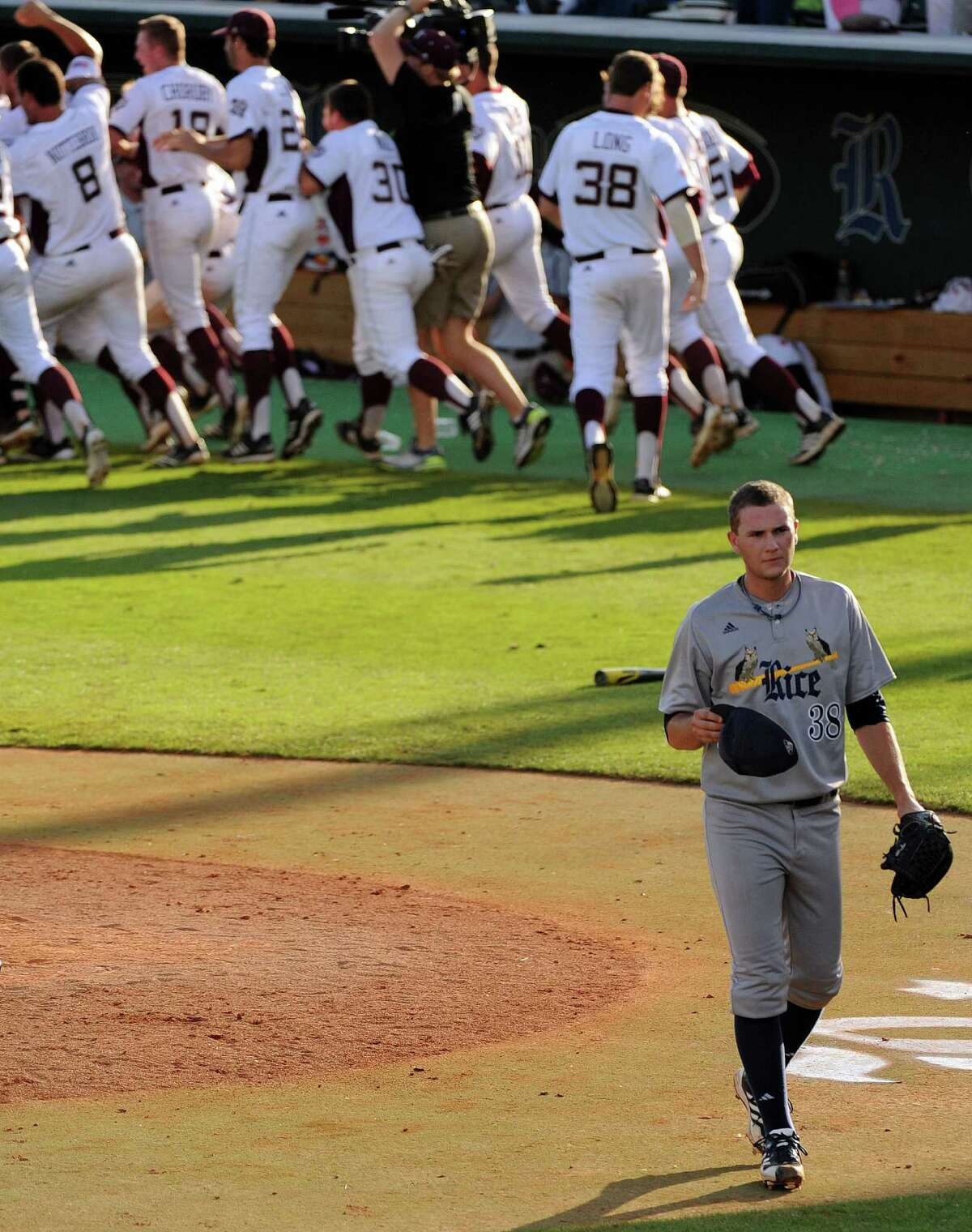 A wild pitch by Rice's Matt Ditman, bottom, allowed the winning run to score in the 10th inning and set off an A&M celebration while ending the Owls' season.