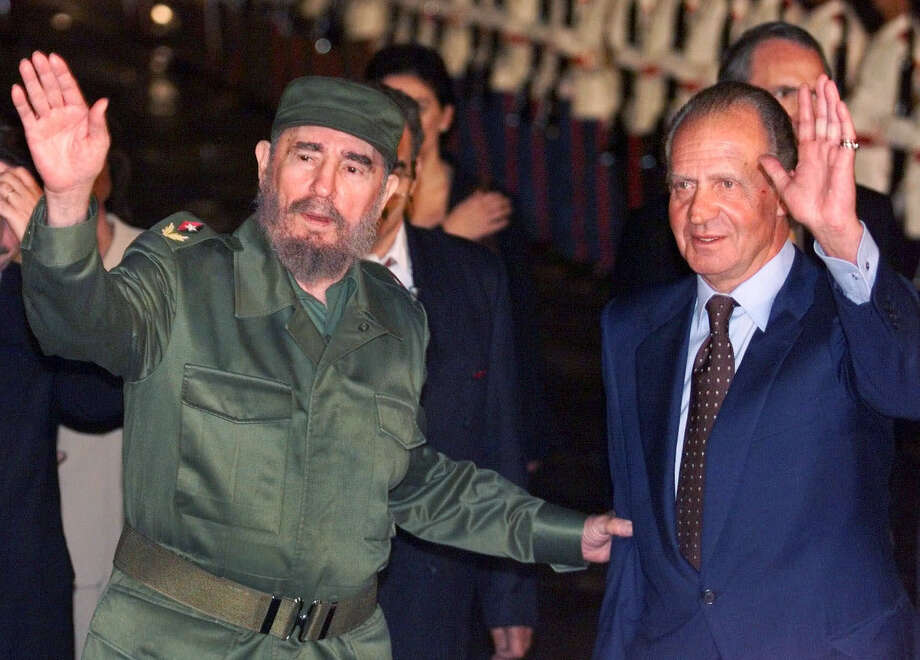 FILE - This is a  Sunday, Nov. 14, 1999 file photo of Cuba's President Fidel Castro, left, and King of Spain Juan Carlos as they wave upon the King's arrival to the Havana's airport . Spain's King Juan Carlos it was announced Monday June 2 2014 will abdicate and pave the way for his son, Crown Prince Felipe, to take over, Spanish Prime Minister Mariano Rajoy told the country Monday in an announcement broadcast nationwide.  He did not say when Juan Carlos would abdicate because the government must now craft a law creating a legal mechanism for the abdication and for 46-year-old Felipe's assumption of power.  The 76-year-old Juan Carlos oversaw his country's transition from dictatorship to democracy but has had repeated health problems in recent years. Photo: RICARDO MAZALAN, AP / AP