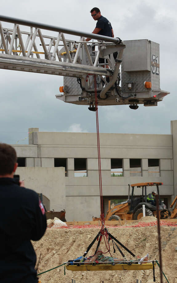 Members of the San Antonio Fire Department's Technical Rescue Team remove an injured construction worker (bottom) Monday June 2, 2014 from a construction site at the corner of La Cantera Parkway and Vance Jackson. Battalion Chief Jonathon Jones said the worker fell before 10:00 a.m. about 15 feet off of a scaffold and was transported to University Hospital after being hoisted out of a structure being built below ground level. Photo: JOHN DAVENPORT, San Antonio Express-News / ©San Antonio Express-News/John Davenport