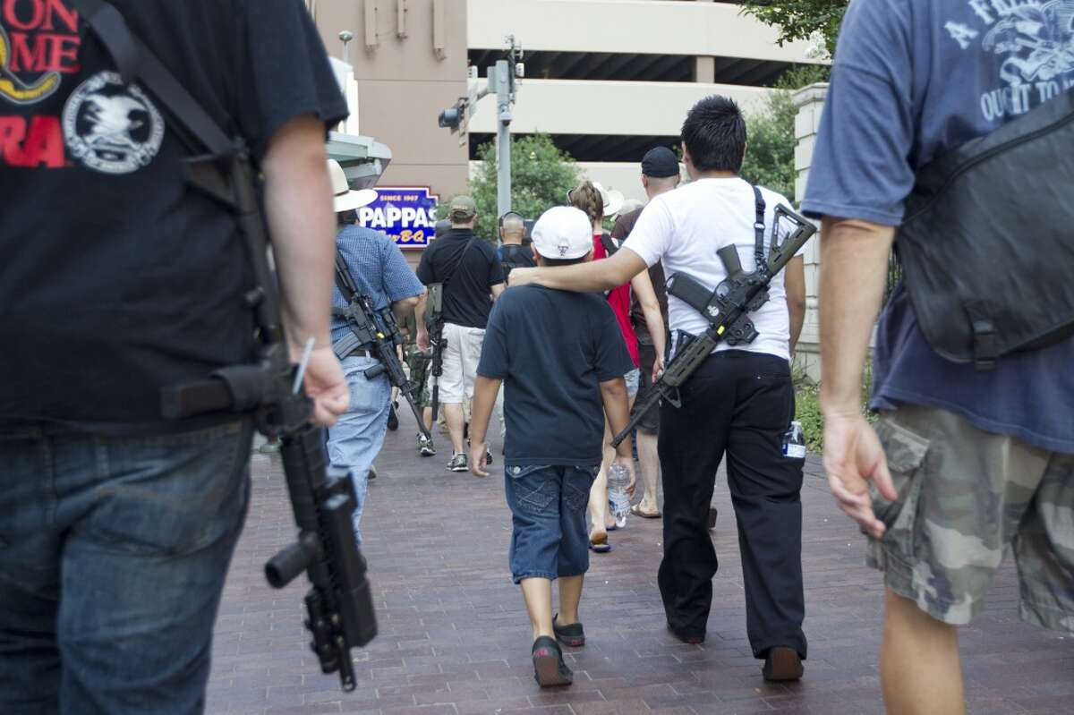 """Jr. Velez, 21, puts his arm around his little brother while walking with his AR-15 rifle down Bagby, as they joined a group of more than 20 people with the pro-gun organization, Come and Take it Houston, as part of a rally to educate people about local gun laws Thursday, July 4, 2013, in Houston. """"This is a Come and Take it Houston walk to help inform citizens about the gun laws here in Texas,"""" co-organizer Kenneth Lindbloom said. """"In Texas there are no restrictions on the open cary of long arms like rifles and shotguns. We want people to realize that in the hands of good people, guns are not dangerous and they don't kill people. When good people have guns it serves as a deterrent to stop crime.""""( Johnny Hanson / Houston Chronicle )"""