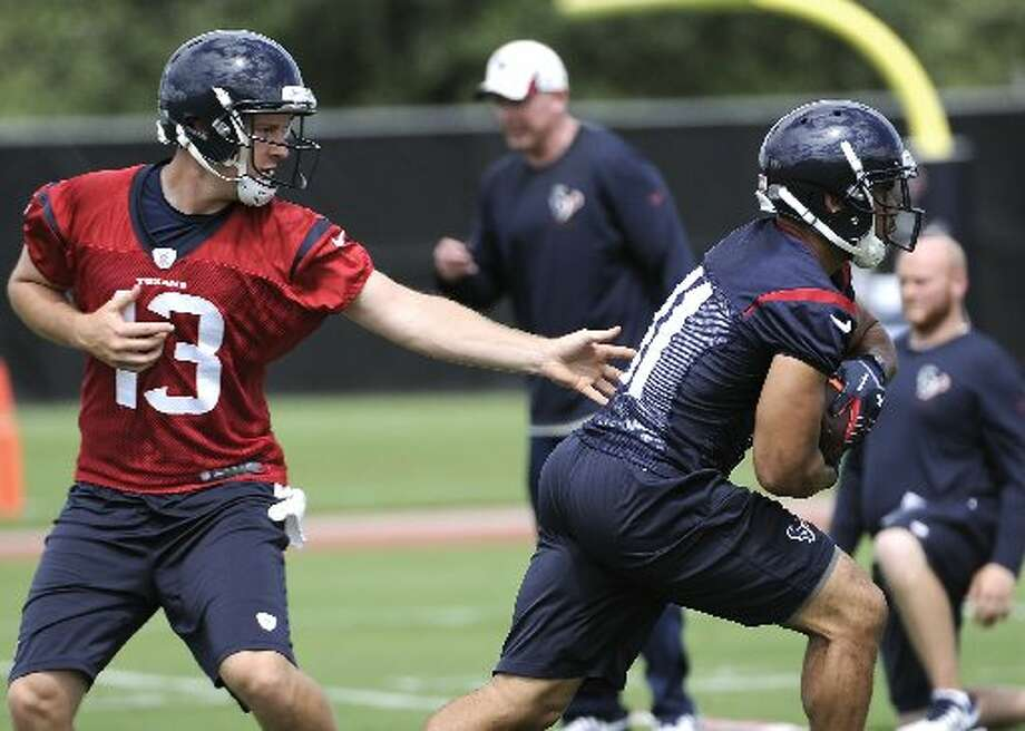 Texans quarterback T.J. Yates hands off the ball to running back Jonathan Grimes. Photo: Pat Sullivan, Associated Press