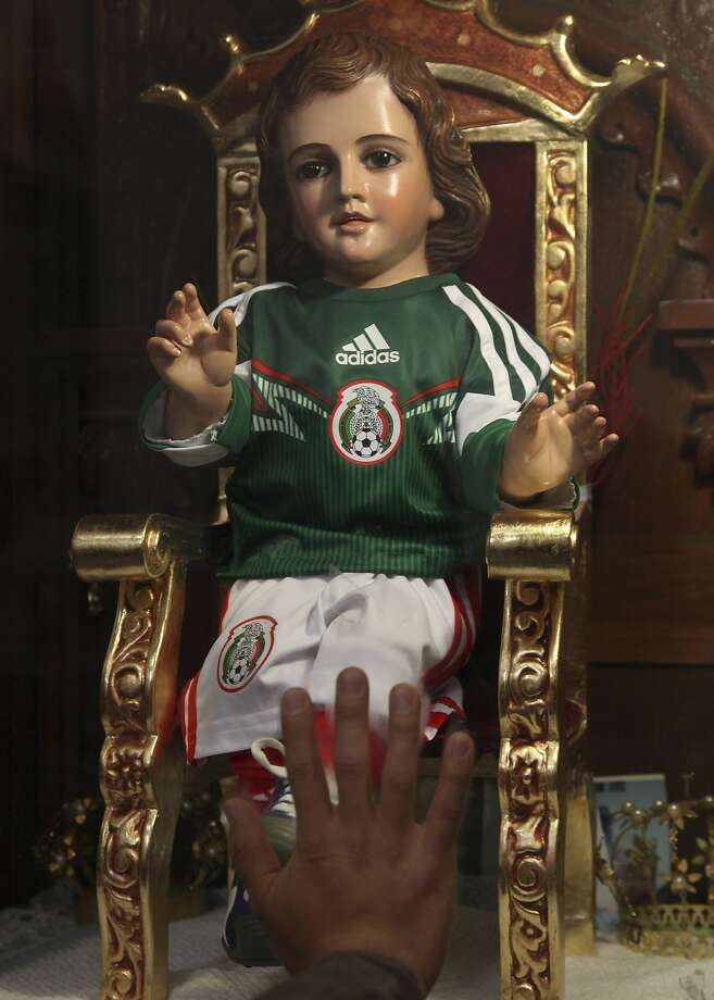 Now we know who God is rooting for in the World Cup:A devotee puts his hand up to the glass case   enshrining a statue of the Santo Nino (Baby Jesus) dressed in the uniform of the Mexican national   team at San Gabriel Archangel Church in Mexico City. Photo: Marco Ugarte, Associated Press