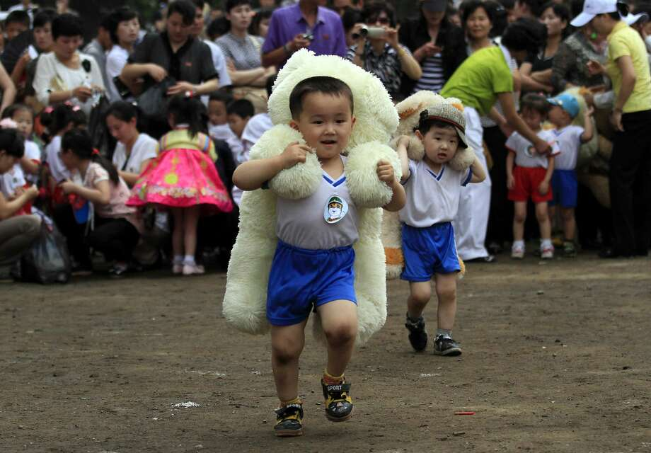 One day he'll be able to tell his grandchildren he won the coveted Stuffed Bear Piggyback:Little boys carrying plush bears sprint to the finish line on International Children's Day at Pyongyang. Photo: Jon Chol Jin, Associated Press