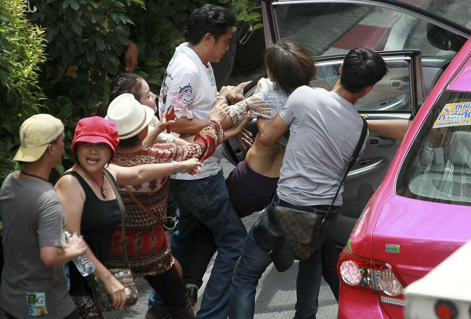 Free cab rides for dissidents: Thai plainclothes police officers wrestle a protester (second from right) into a taxi during an 