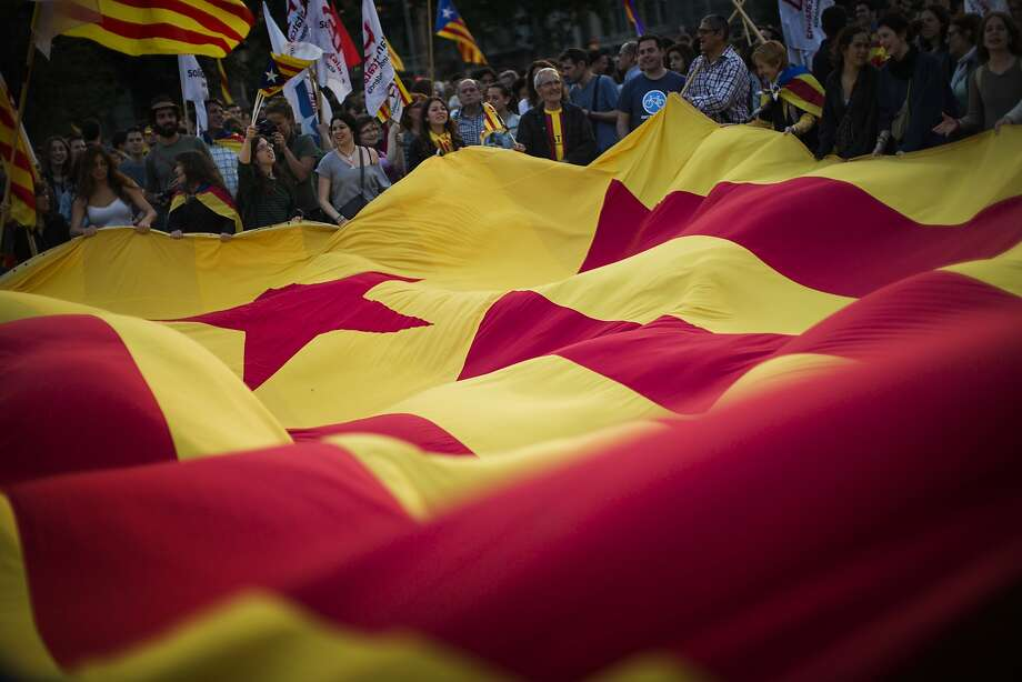 After the abdication announcement by Spain's King Juan Carlos, demonstrators wave a pro-independence flag during a Barcelona protest calling for Catalonia's secession. Photo: Emilio Morenatti, Associated Press