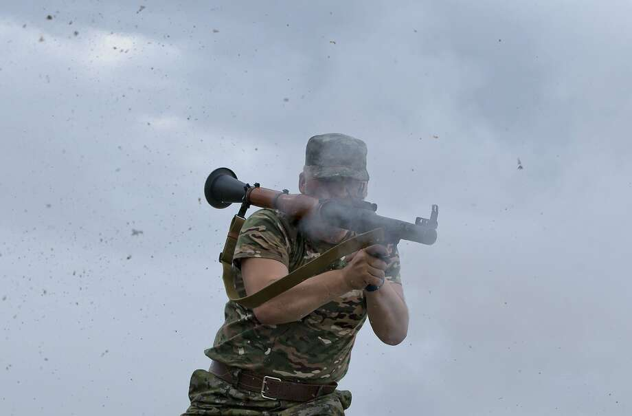 A pro-Russian rebel fires a rocket propelled grenade on the rooftop of an apartment building during clashes with Ukrainian troops on the outskirts of Luhansk, Ukraine, Monday, June 2, 2014. Hundreds of pro-Russia insurgents attacked a border guard base in eastern Ukraine on Monday, with some firing rocket-propelled grenades from the roof of a nearby residential building. At least five rebels were killed when the guards returned fire, a spokesman for the border guard service said.(AP Photo/Vadim Ghirda) Photo: Vadim Ghirda, Associated Press