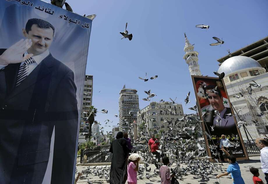"TOPSHOTS Syrians feed pigeons on a square where are displayed giant campaign billboards bearing portraits of Syrian President Bashar al-Assad on June 1, 2014 in the capital Damascus. Syria began its last day of campaigning for the June 3 presidential elections expected to return incumbent Bashar al-Assad to power, a vote the opposition has labelled a ""parody of democracy"". AFP PHOTO/JOSEPH EIDJOSEPH EID/AFP/Getty Images Photo: Joseph Eid, AFP/Getty Images"