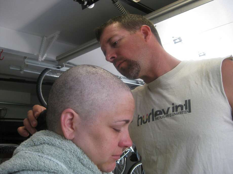 Arrica Wallace of Manhattan, Kan., has her head shaved by husband Matthew in August 2012, when her hair was falling out from cancer treatment. She is now cancer free after an immunotherapy trial. Photo: Uncredited, Associated Press