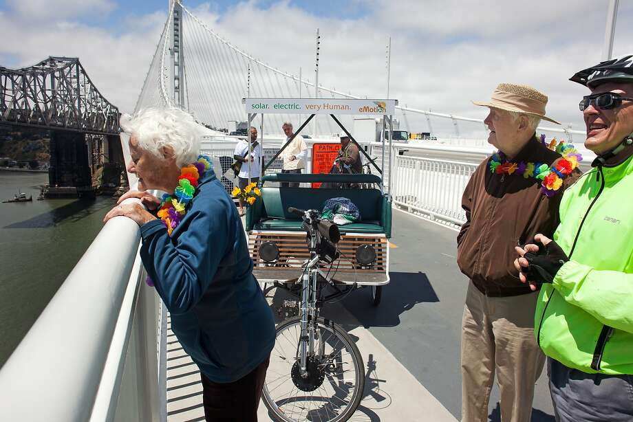 Char Schneider, left, peers over the edge of the bay bridge after pedicab ride to the end of the Bay Bridge bike path. Photo: Tim Hussin, Special To The Chronicle