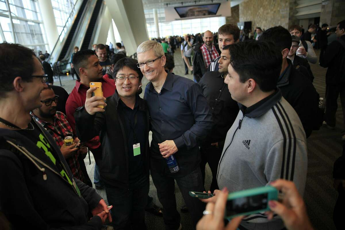 Apple chief executive officer Tim Cook (center) poses for photos with WWDC attendees after speaking during the keynote for the Apple Worldwide Developers Conference 2014 at Moscone West in San Francisco, Calif.
