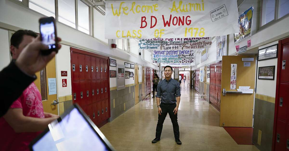 BD Wong has his photo taken under a banner welcoming him back to his alma mater, Abraham Lincoln High School, on Wednesday, May 7, 2014 in San Francisco, Calif. Wong graduated from the school in 1978.