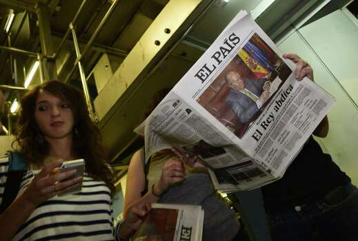 Journalists read  a special edition of the Spanish newspaper El Pais following the abdiction of King Juan Carlos in Madrid on June 2, 2014. Spanish King Juan Carlos announced his abdication on June 2, 2014 in favour of his son Prince Felipe, ending a 39-year reign that guided Spain from dictatorship to democracy but was later battered by royal scandals.  AFP PHOTO/ PIERRE-PHILIPPE MARCOUPIERRE-PHILIPPE MARCOU/AFP/Getty Images Photo: PIERRE-PHILIPPE MARCOU, AFP/Getty Images / AFP