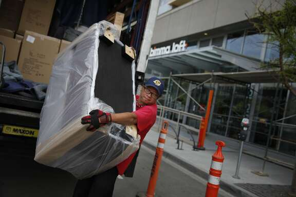 Karl Wong, Apex Fleet Service owner, carries a delivery into Bimma Loft on Friday, May 23, 2014 in San Francisco, Calif.  Bimma Loft opened it's store on March 10, 2014 and the Mission Bay construction project fire occurred the next day on March 11, 2014.