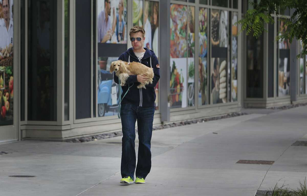 Steven Johnson, who lives in the Mission Bay neighborhood, walks along Fourth Street as he carries his dog Lena, as they walk past signage on a storefront for The Market Hall on Friday, May 23, 2014 in San Francisco, Calif.