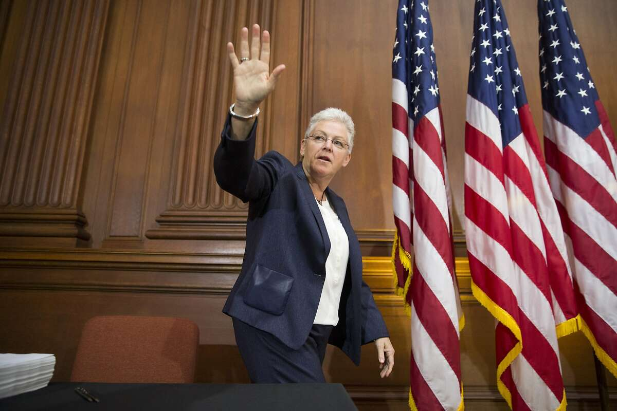 Environmental Protection Agency (EPA) Administrator Gina McCarthy waves before signing new emission guidelines during an announcement of a plan to cut carbon dioxide emissions from power plants by 30 percent by 2030, Monday, June 2, 2014, at EPA headquarters in Washington. In a sweeping initiative to curb pollutants blamed for global warming, the Obama administration unveiled a plan Monday that cuts carbon dioxide emissions from power plants by nearly a third over the next 15 years, but pushes the deadline for some states to comply until long after President Barack Obama leaves office. (AP Photo/ Evan Vucci)