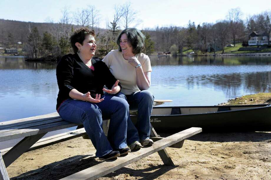 Velya Jancz-Urban, left, and Elizabeth Vill Cole are childhood friends. Here they share some memories near Rainbow Lake in Ridgefield, where they spent much of their youth. After losing touch for more than 30 years, they recently found each other again. Photo: Carol Kaliff / The News-Times