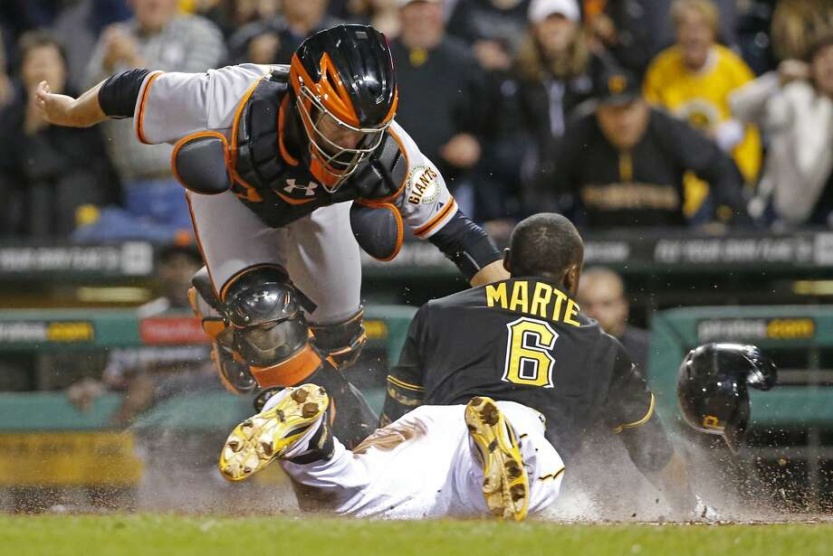 The Pirates' Starling Marte, originally called out, scores ahead of the tag by the Giants' Buster Posey. Photo: Gene J. Puskar, Associated Press