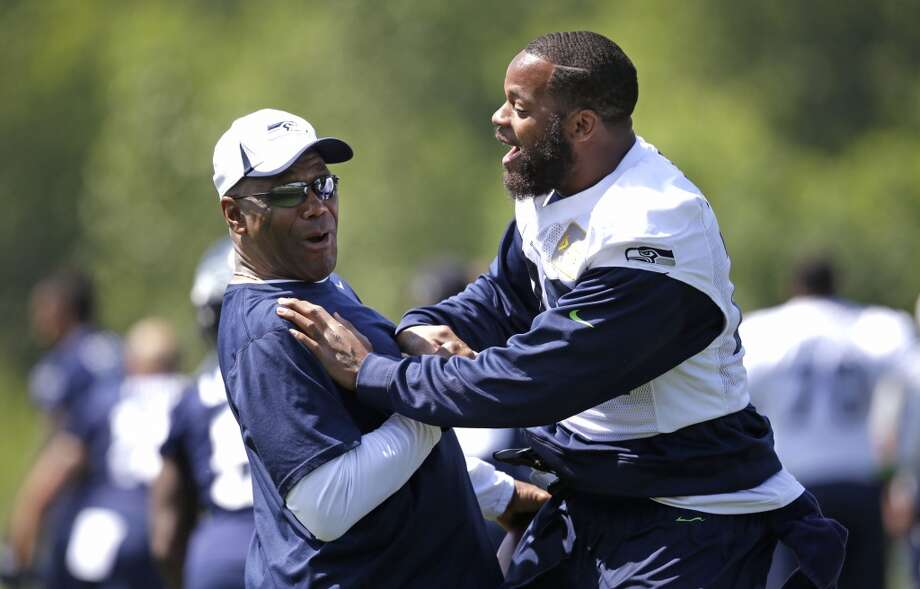 Seattle Seahawks defensive end Michael Bennett, right, shares a laugh with running backs coach Sherman Smith at the beginning of Seahawks OTAs on Monday. Photo: Elaine Thompson, Associated Press