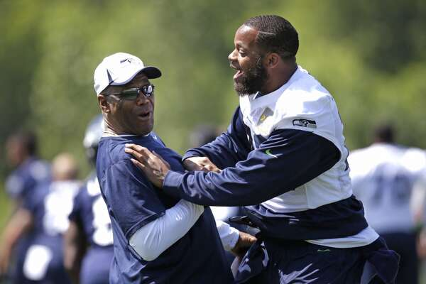 Seattle Seahawks defensive end Michael Bennett, right, shares a laugh with running backs coach Sherman Smith at the beginning of Seahawks OTAs on Monday.