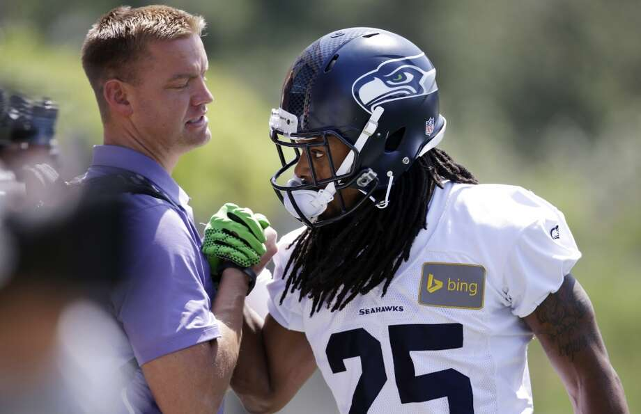 Seattle Seahawks cornerback Richard Sherman, right, greets former NFL quarterback and broadcaster Brock Huard before Seahawks OTAs on Monday. Photo: Elaine Thompson, Associated Press