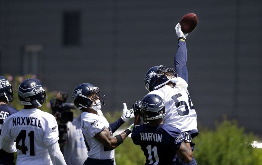 Seattle Seahawks linebacker Bobby Wagner (54) knocks the ball away in front of Percy Harvin (11) at Seahawks OTAs on Monday. Photo: Elaine Thompson, Associated Press