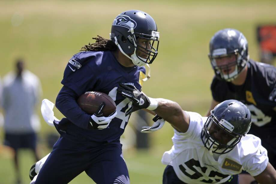 Seattle Seahawks wide receiver Arceto Clark, left, runs with the ball as Malcolm Smith defends at Seahawks OTAs on Monday. Photo: Elaine Thompson, Associated Press