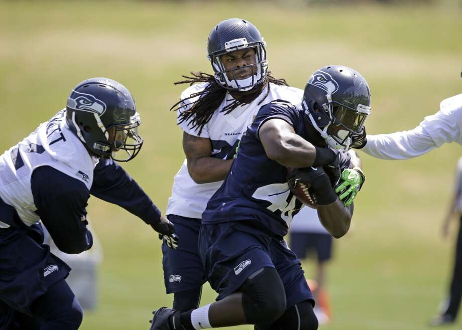 Seattle Seahawks defensive end Michael Bennett, left, and cornerback Richard Sherman chase running back Derrick Coleman at Seahawks OTAs on Monday. Photo: Elaine Thompson, Associated Press