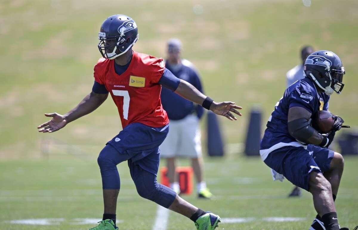 Seattle Seahawks quarterback Tarvaris Jackson (7) continues running after handing off to Robert Turbin at Seahawks OTAs on Monday.