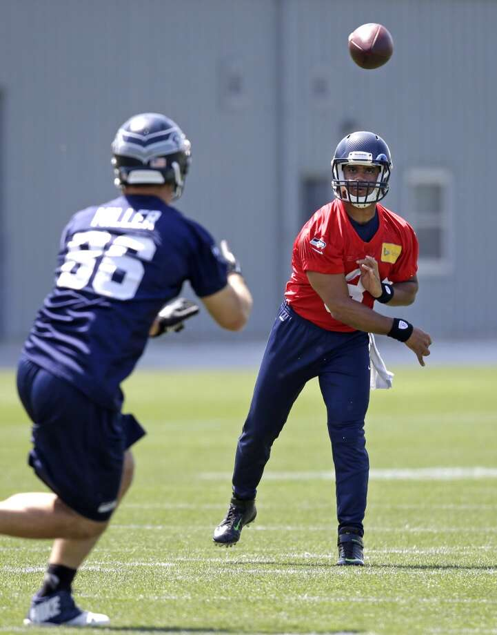 Seattle Seahawks quarterback Russell Wilson, right, passes to Zach Miller at Seahawks OTAs on Monday. Photo: Elaine Thompson, Associated Press