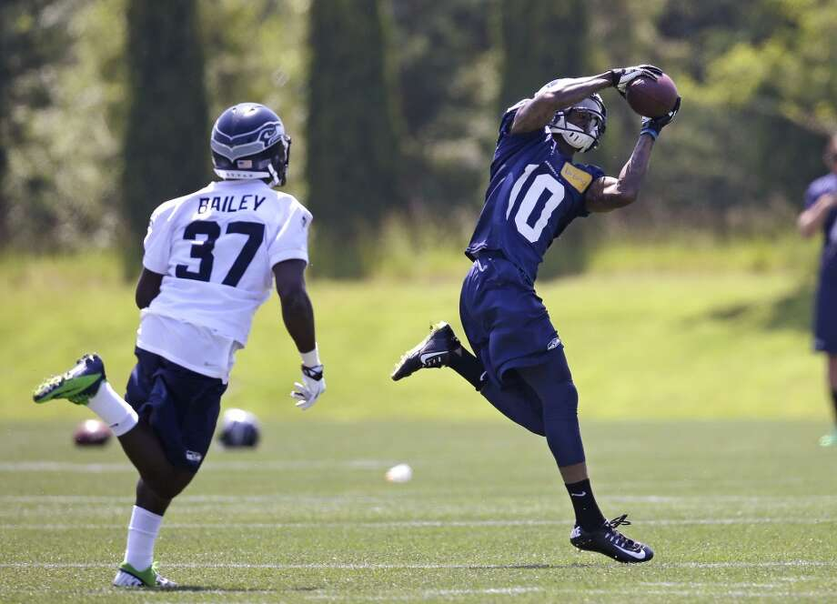 Seattle Seahawks wide receiver Paul Richardson (10) makes a catch as Dion Bailey defends at Seahawks OTAs on Monday. Photo: Elaine Thompson, Associated Press