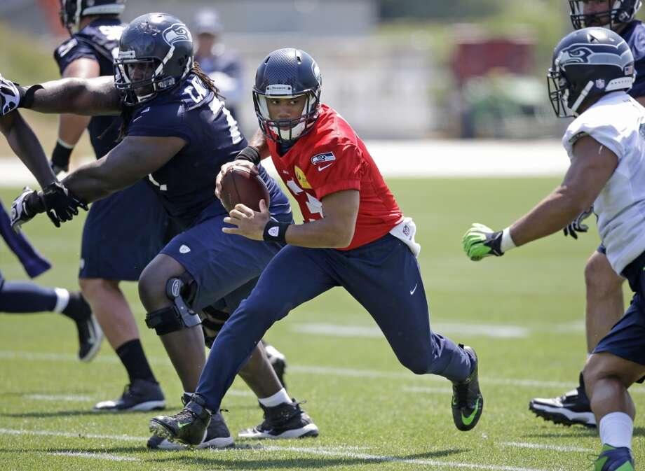 Seattle Seahawks quarterback Russell Wilson scrambles at Seahawks OTAs on Monday. Photo: Elaine Thompson, Associated Press