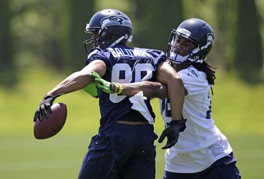Seattle Seahawks cornerback Richard Sherman, right, reaches around to try and knock the ball away from receiver Doug Baldwin during a drill at Seahawks OTAs on Monday. Photo: Elaine Thompson, Associated Press