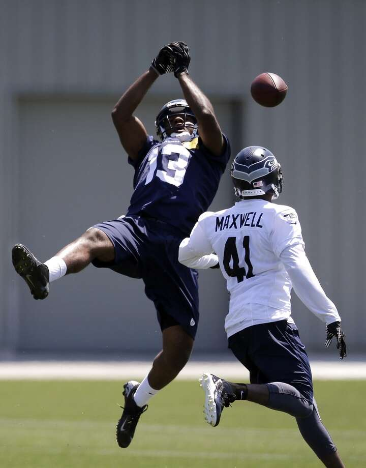 Seattle Seahawks wide receiver Chris Matthews (13) drops a pass as cornerback Byron Maxwell defends at Seahawks OTAs on Monday. Photo: Elaine Thompson, Associated Press