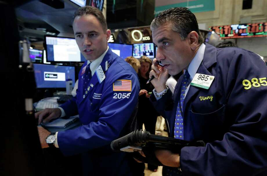 Specialist Jason Hardzewicz, left, and trader Vincent Quinones work on the floor of the New York Stock Exchange Monday, June 2, 2014. Stocks were moving slightly lower in early trading Monday following the release of a closely watched report that showed an unexpected slowdown in U.S. manufacturing last month. The market is coming off record highs last week. (AP Photo/Richard Drew) ORG XMIT: NYRD110 Photo: Richard Drew / AP