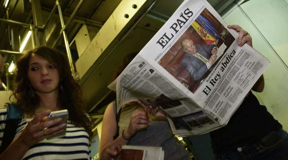 Journalists read a special edition of the Spanish newspaper El Pais following the abdication announcement of King Juan Carlos. Photo: Pierre-Philippe Marcou / AFP / Getty Images / AFP