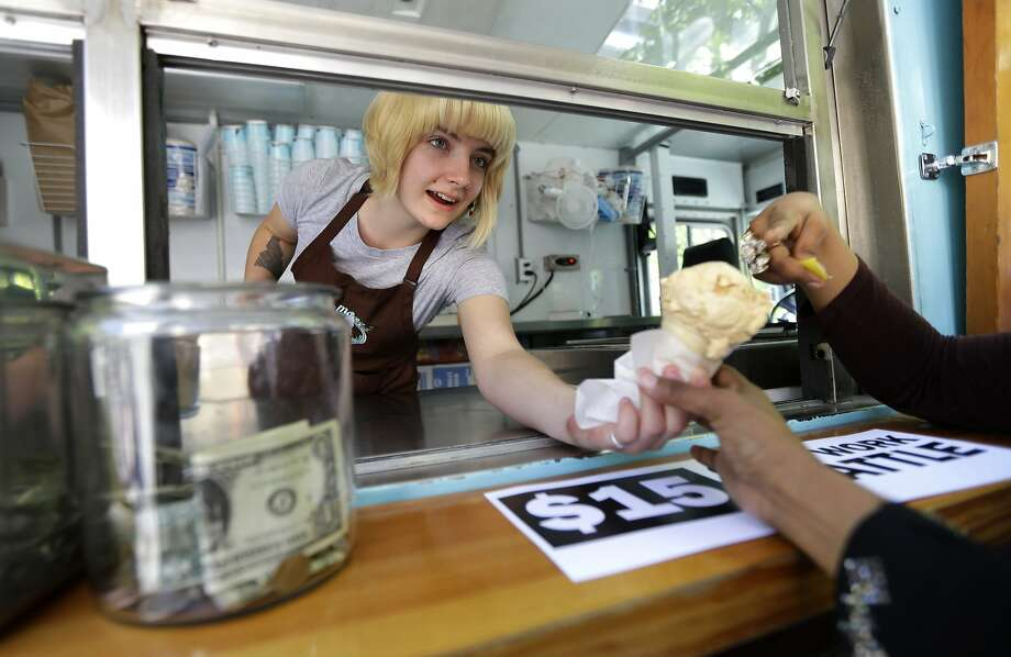 Caitlyn Faircloth hands out free ice cream at a rally outside Seattle City Hall celebrating the minimum wage increase. Photo: Ted S. Warren, Associated Press