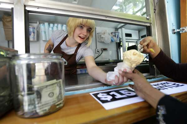 Caitlyn Faircloth, a worker with Molly Moon's Homemade Ice Cream, hands out free ice cream next to a tip jar, Monday, June 2, 2014, at a rally celebrating the passage of a $15 minimum wage measure outside Seattle City Hall in Seattle. The Seattle City Council passed a $15 minimum wage measure, Monday, but not until after debate over how long businesses will have to phase in the measure, and how tips, benefits, and other forms of compensation will be considered. (AP Photo/Ted S. Warren)