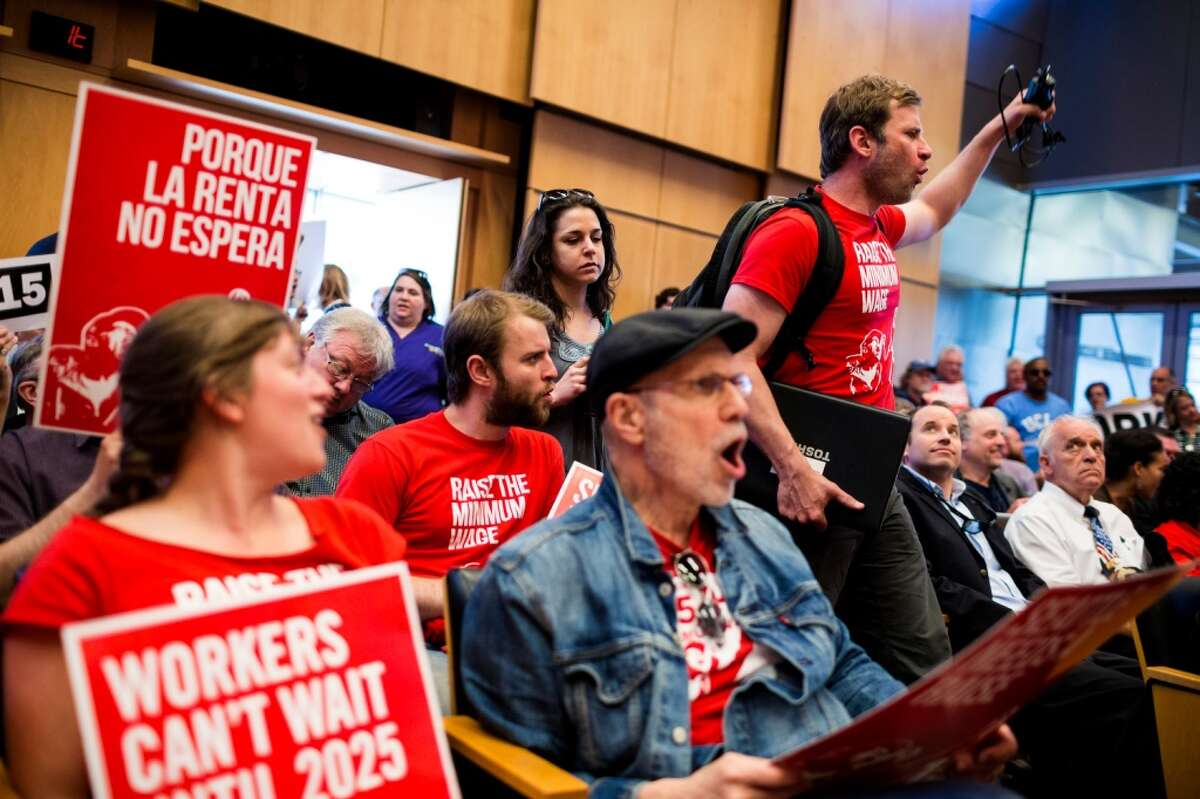 Inside the Council chamber, supporters make a racket in favor of the 15-dollar-an-hour minimum wage for Seattle employers, large and small, on Monday, June 2, 2014, at City Hall in Seattle. Phased in over the next seven years, Seattle will have the highest minimum wage in America. (Jordan Stead, seattlepi.com)